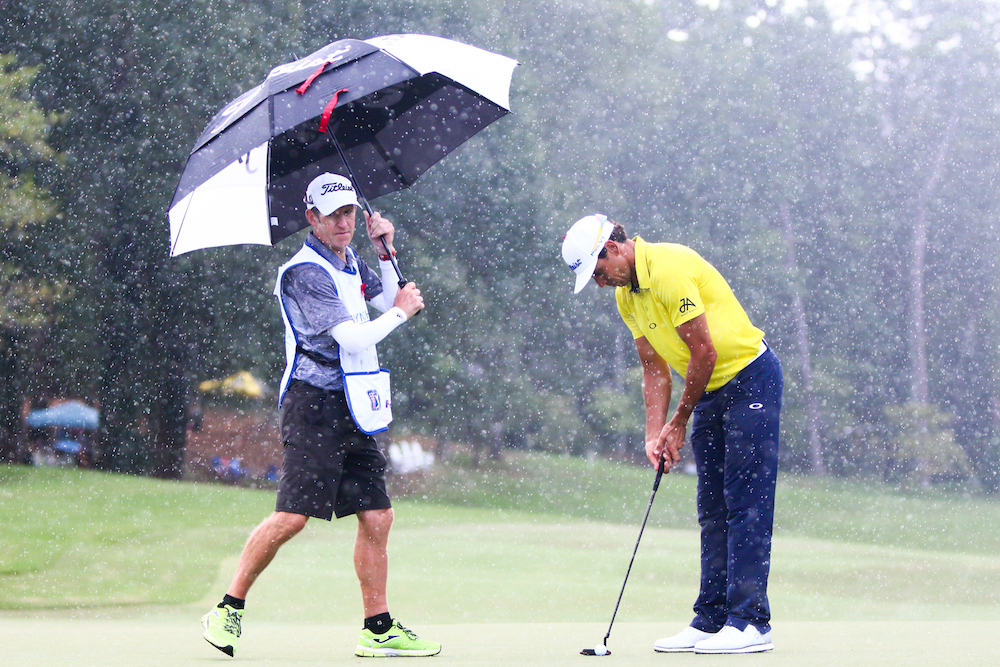 Mike Batty holds an umbrella while Rafa Cabrera Bello lines up a shot. Sedgefield Country Club hosted the 2016 Wyndham Championship on August 21, 2016 in Greensboro, North Carolina.(Jerome Carpenter/WRAL Contributor)